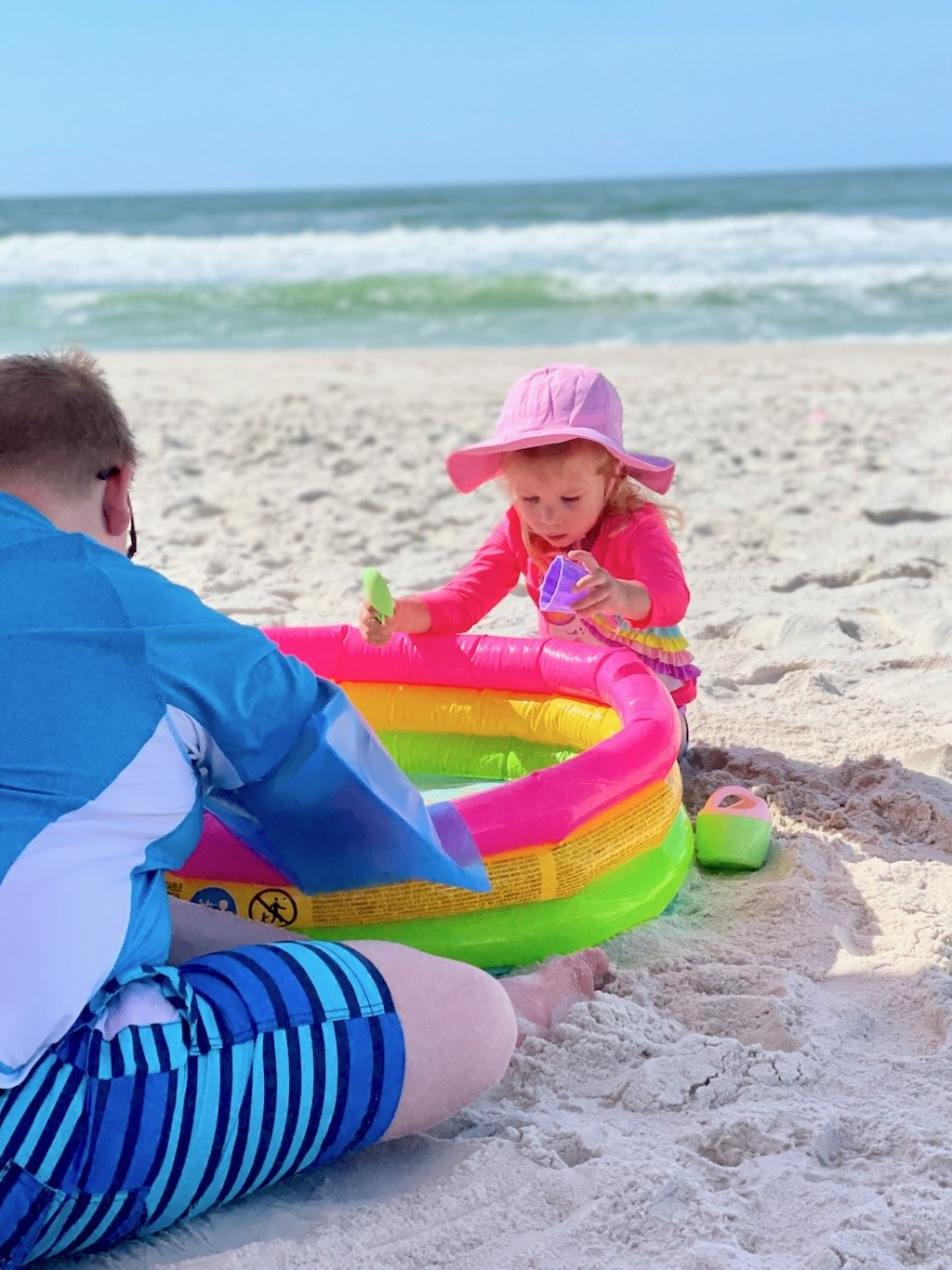 two kids playing with an inflatable pool at the beach